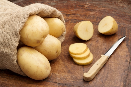 raw potatoes and fnife on a wooden background