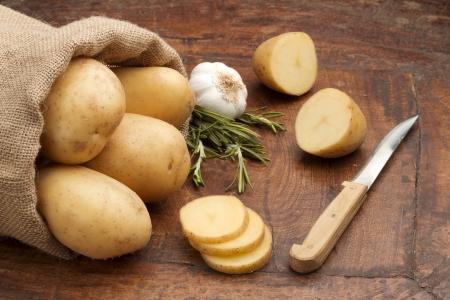 sliced raw potatoes, rosemary and bulb of garlic