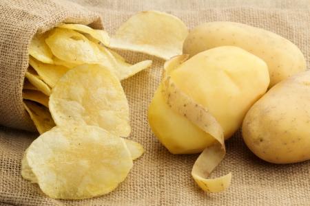 raw potato: chips and peeled potato on a jute texture