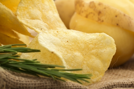 raw potato: close up of chips, rosemary and raw potato on a jute background Stock Photo