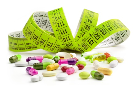 vitamins pills: tape measure and medicine colored on white background