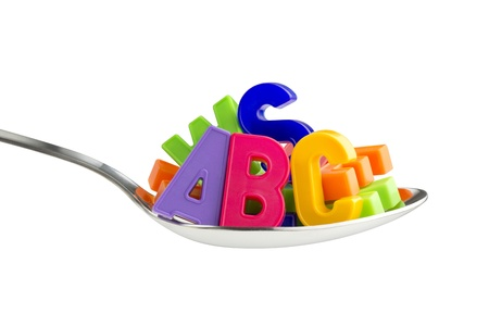 playtime: colorful letters in a tablespoon on white background Stock Photo