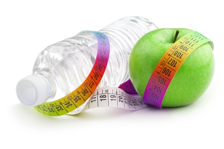 bottle of water and green apple wrapped by a colorful measuring tape Imagens