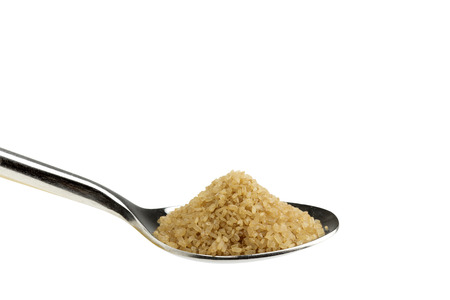 close up of a teaspoon of brown sugar on white background