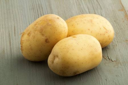 raw potatoes isolated on wooden background photo