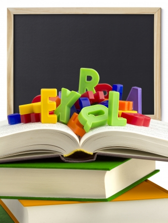 grammar: stack of books, colored letters and a blackboard in the background Stock Photo