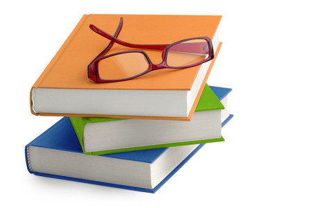 stack of books with a pair of eyeglasses on top Stock Photo