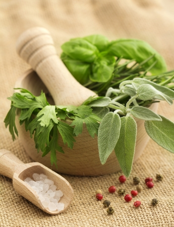 fragrant scents: mortar and pestle with herbs and spices on a jute background