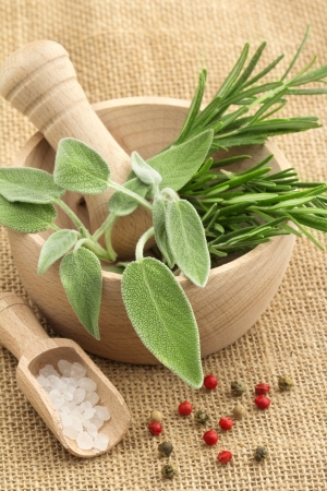 sage: mortar and pestle with herbs and spices on a jute background