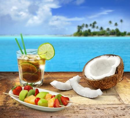 Cuba libre y frutas tropicales en una mesa de madera en un paisaje marino polinesio