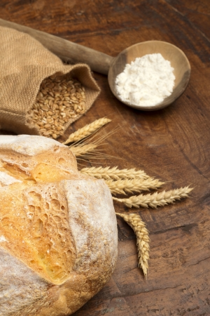 bread, ears, flour and grains of wheat on wooden table photo