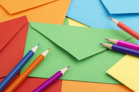 background of colorful envelopes and colored pencils photo