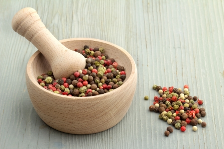mortar and pestle with peppercorn mix on wooden table photo