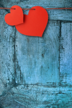 two heart-shaped cards hanging  on a blue plank photo