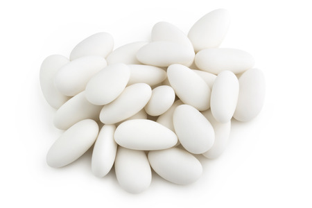 heap of white sugared almonds on white background photo