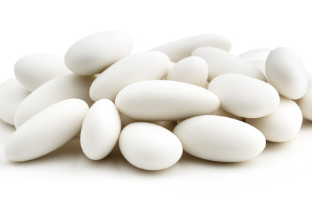 sugared: heap of  white sugared almonds on white background