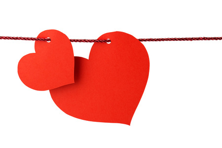 love story: two cards in the shape of heart hanging from a red cord