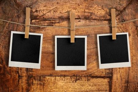 drie snapshots opknoping van een touw over een antieke houten bord Stockfoto