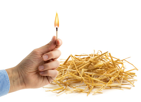 kindle: hand holding a burning matchstick near a haystack Stock Photo