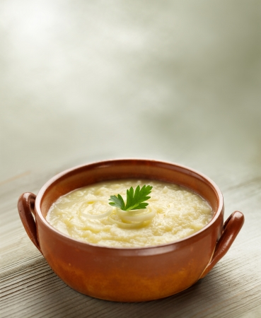 potato soup: steaming bowl of potato soup on wooden table