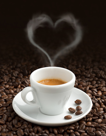 coffee cup with heart-shaped steam on coffee beans Фото со стока