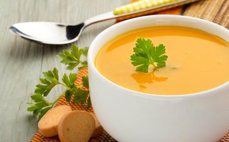 나무 테이블에 수프, 파슬리의 그릇 크루통