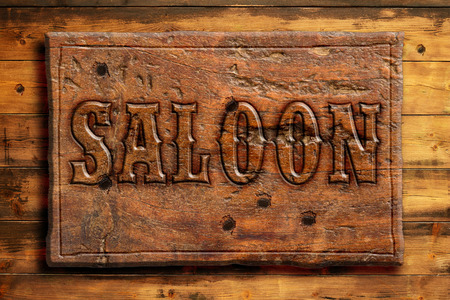 the western wall: signboard of saloon on a wooden wall