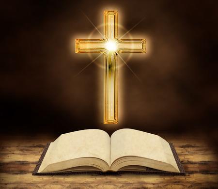 vangelo aperto: bibbia e crocifisso incandescente su sfondo scuro in legno