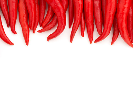 tabasco: row of red chillies on white background