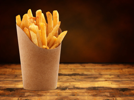 french fries in a paper basket on wooden table Banco de Imagens