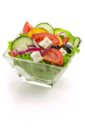 fresh vegetable salad in a glass bowl on white background photo