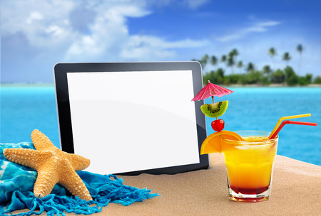 tablet, sea star and tropical cocktail in the sand