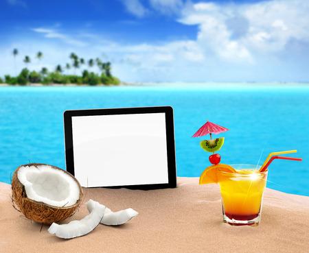 tabletta, kókusz és koktél a homokban Stock fotó