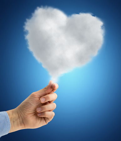 male hand holding a heart-shaped cloud on blue background photo