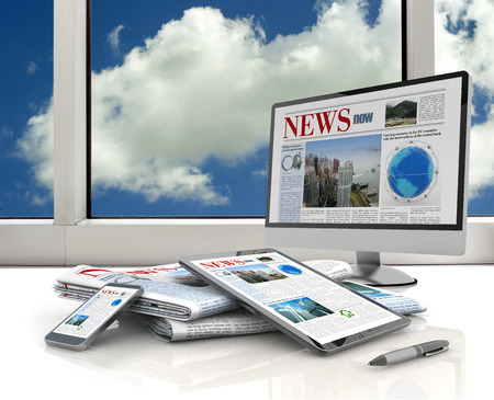 pc, tablet, cell phone and daily newspaper on white desk photo