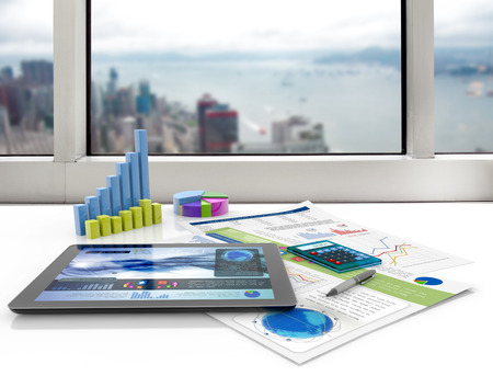 accounting design: tablet and financial graphs on a white desk Stock Photo