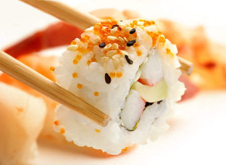 close up of chopsticks with california roll photo