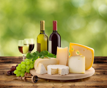 cheeseboard, grape and wine on wooden table in countryside