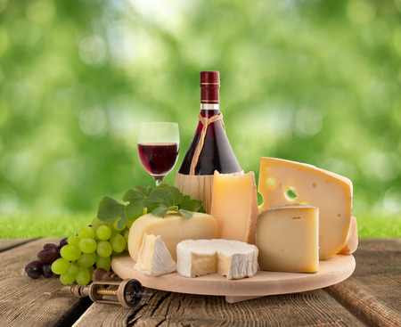 emmental: cheese board, grape and red wine on wooden table