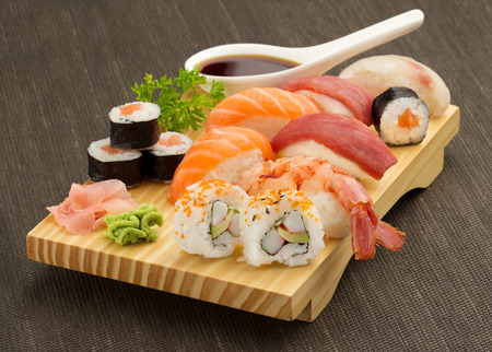 roll bar: japanese seafood sushi and maki on wooden plate