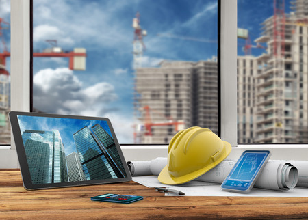 tablet, smartphone, safety helmet and blueprints in construction site Foto de archivo