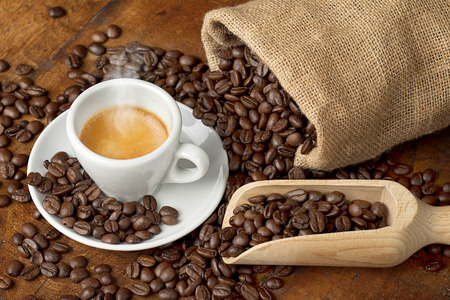 coffee cup with jute bag and spoon full of coffee beans photo