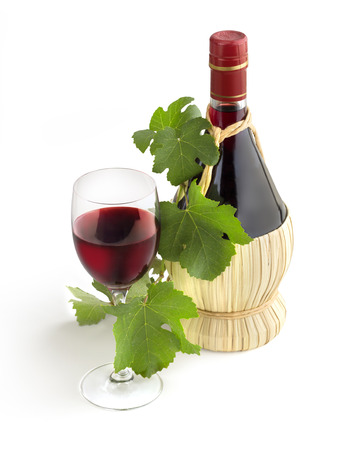 classic Chianti bottle, wineglass and grapevine leaves photo