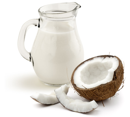 jug of coconut milk and half coconut on white background