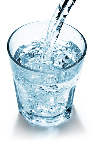 vaso de agua: chorro de agua que llena un vaso sobre fondo blanco