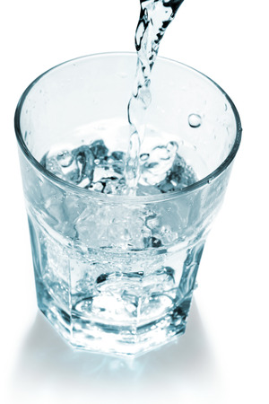 vasos de agua: chorro de agua que llena un vaso sobre fondo blanco