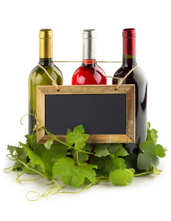 blackboard hanging on wine bottles and grapevine leaves photo