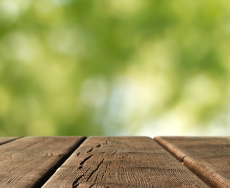 landscape garden: wooden table top in a blurred country landscape