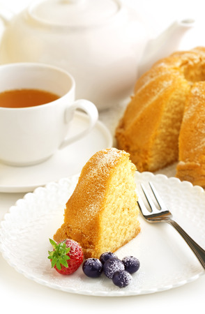 slice of donut, cup of tea and teapot Stockfoto