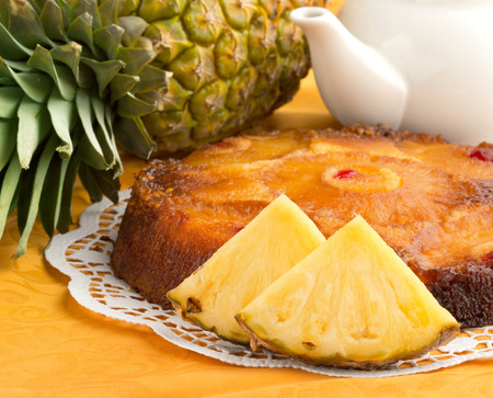 upside down cake and fresh pineapple on orange tablecloth